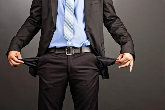 Man in suit showing his empty pant pockets