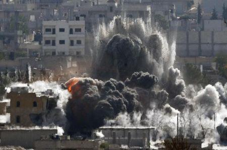 An explosion following an air-strike is seen in the Syrian town of Kobani during heavy fighting