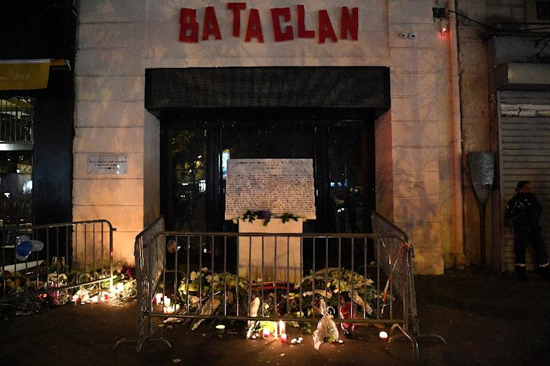 A picture taken on November 13, 2017 shows a makeshift memorial around the commemorative plaque outside the Bataclan venue