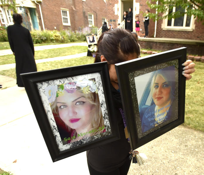 A woman who wishes not to be identified carries portraits of Saja Aljanabi to her makeshift memorial on Bingham St., in Dearborn, Mich., Sunday, Sept. 8, 2019. Dearborn Police Chief Ronald Haddad said Thursday, Sept. 12, 2019, that the 14-year-old, a 13-year-old and 17-year-old are being held in connection with last week's killing of Saja Aljanabi and they could be involved in other crimes in the area. (Todd McInturf/Detroit News via AP)