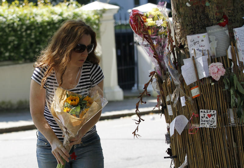 A fan of British singer songwriter Amy Winehouse leaves flowers for her outside her house in London on the first anniversary of her death, Monday, July 23, 2012. (AP Photo/Sang Tan)