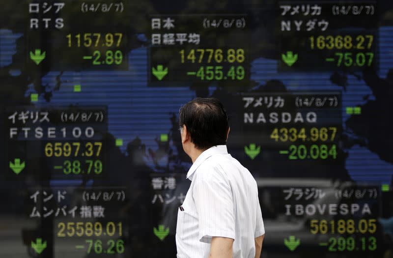 A pedestrian looks at an electronic board showing the stock market indices of various countries outside a brokerage in Tokyo