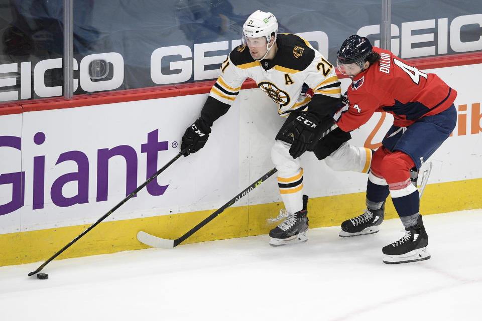 Boston Bruins left wing Nick Ritchie (21) and Washington Capitals defenseman Brenden Dillon (4) battle for the puck during the first period of an NHL hockey game, Tuesday, May 11, 2021, in Washington. (AP Photo/Nick Wass)