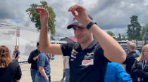 Rinus VeeKay lifts his arms at Mid-Ohio Sports Car Course, Friday, July 2, 2021, in Lexington, Ohio, to show his range of motion is fine after surgery to repair a broken collarbone. VeeKay missed one race after falling from his bicycle during a training ride but will be back in his car Sunday for IndyCar's race on the road course. (AP Photo/Jenna Fryer)