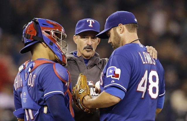 Texas Rangers pitching coach Mike Maddux, center, talks with starting pitcher Colby Lewis (48) as catcher Robinson Chirinos listens after Lewis gave up a pair of hits to the Seattle Mariners in the fourth inning of a baseball game on Saturday, April 26, 2014, in Seattle. (AP Photo/Elaine Thompson)