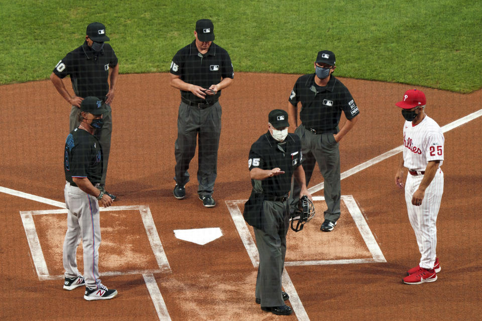 FILE - In this Friday, July 24, 2020, file photo, home plate umpire Tim Timmons, center, explains things to Miami Marlins manager Don Mattingly, left, and Philadelphia Phillies manager Joe Girardi, right, with the other umpires looking on prior to a baseball game in Philadelphia. The Miami Marlins' coronavirus outbreak could endanger the Major League Baseball season, Dr. Anthony Fauci said, as the number of their players testing positive rose to 15. The Marlins received positive test results for four additional players Tuesday, July 123, 2020, a person familiar with the situation told The Associated Press. The person declined to be identified because the results had not been publicly released.  (AP Photo/Chris Szagola, File)