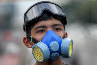 A frontline pro-democracy activist wearing a protective gas-mask looks on during a demonstration at Kaset intersection, suburbs of Bangkok, Thailand, Monday, Oct. 19, 2020. Thailand's embattled Prime Minister Prayuth Chan-ocha said Monday that there were no plans to extend a state of emergency outside the capital, even as student-led protests calling for him to leave office spread around the country. (AP Photo/Sakchai Lalit)