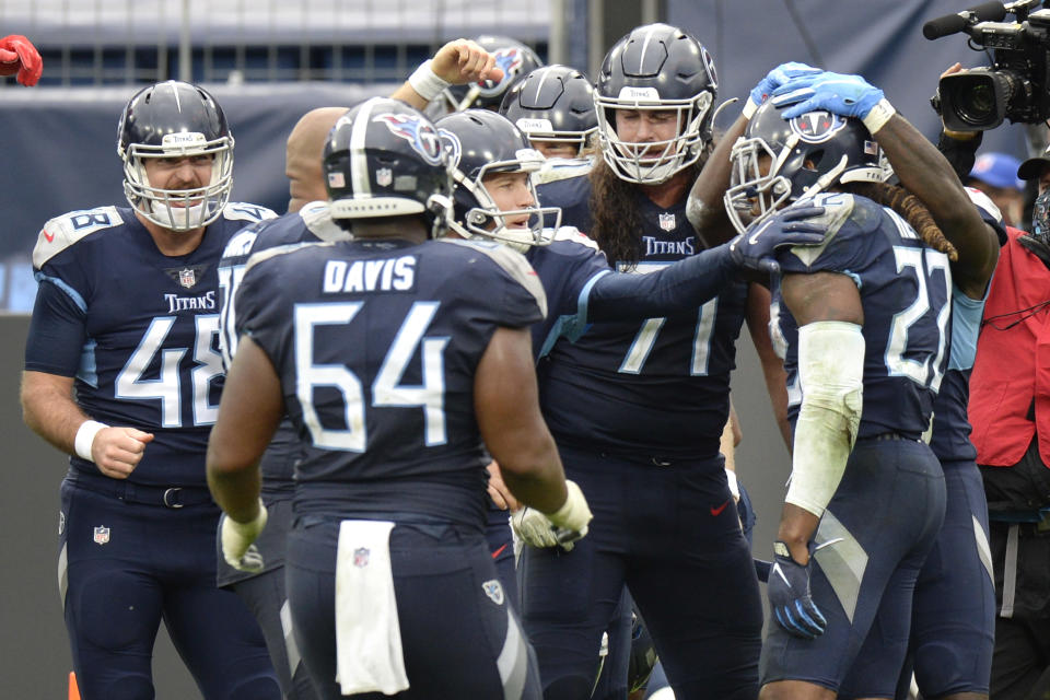 Tennessee Titans running back Derrick Henry (22) is mobbed by teammates after Henry scored the winning touchdown against the Houston Texans in overtime of an NFL football game Sunday, Oct. 18, 2020, in Nashville, Tenn. The Titans won 42-36. (AP Photo/Mark Zaleski)