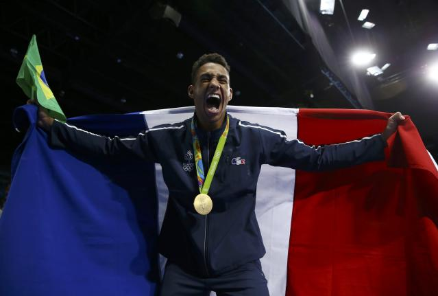 2016 Rio Olympics - Boxing - Victory Ceremony - Men's Super Heavy (+91kg) Victory Ceremony - Riocentro - Pavilion 6 - Rio de Janeiro, Brazil - 21/08/2016. Gold medallist Tony Yoka (FRA) of France celebrates while holding the his national flag. REUTERS/Peter Cziborra FOR EDITORIAL USE ONLY. NOT FOR SALE FOR MARKETING OR ADVERTISING CAMPAIGNS.