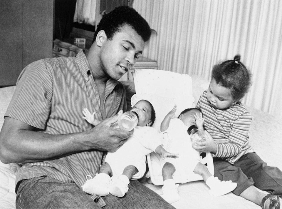 <p>Muhammad Ali and his daughter Maryum feed his 10-week-old twins, Reeshemah and Jamilah, in their Philadelphia home in 1970.</p>