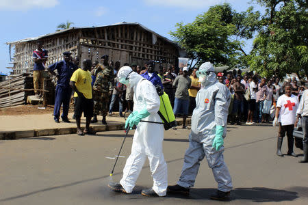 Health workers spray themselves with chlorine disinfectants after removing the body a woman who died of Ebola virus in the Aberdeen district of Freetown