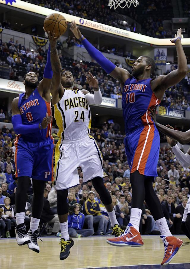 Indiana Pacers forward Paul George, center, shoots between Detroit Pistons center Andre Drummond, left, and forward Greg Monroe in the second half of an NBA basketball game in Indianapolis, Monday, Dec. 16, 2013. The Pistons defeated the Pacers 101-96. (AP Photo/Michael Conroy)