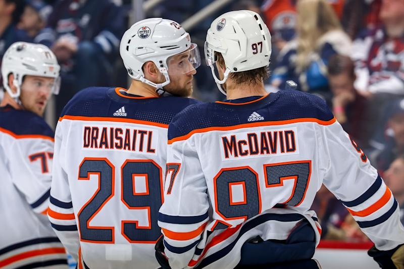 WINNIPEG, MB - OCTOBER 20: Leon Draisaitl #29 and Connor McDavid #97 of the Edmonton Oilers discuss strategy during a first period stoppage in play against the Winnipeg Jets at the Bell MTS Place on October 20, 2019 in Winnipeg, Manitoba, Canada. (Photo by Jonathan Kozub/NHLI via Getty Images)