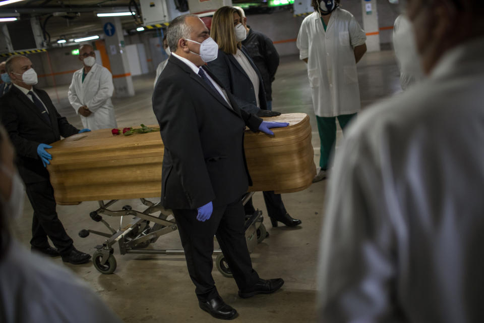 Mortuary service workers carry the coffin of the last COVID-19 victim stored at an underground parking garage that was turned into a morgue, at the Collserola funeral home in Barcelona, Spain. May 17, 2020. A funeral home in Barcelona has closed a temporary morgue it had set up inside its parking garage to keep the victims of the Spanish city's coronavirus outbreak. The last coffin was removed and buried on Sunday. In 53 days of use, the temporary morgue has held more than 3,200 bodies. (AP Photo/Emilio Morenatti)