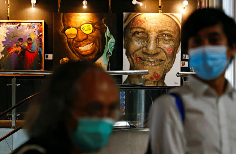 FILE PHOTO: Visitors wearing protective face masks walk past painted art during an exhibition, amid the coronavirus disease (COVID-19) outbreak, in Jakarta