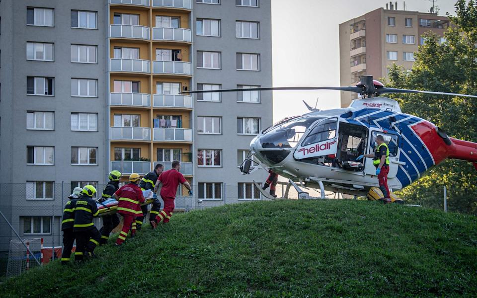 Firefighters carry a stretcher to a waiting helicopter at the scene where a fire broke out in an apartment block - AFP
