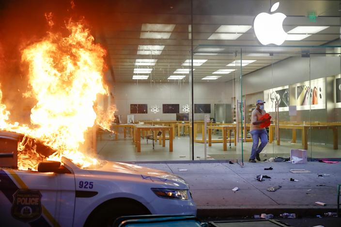 A person leaves the Apple Store as a police car burns during the Justice for George Floyd Philadelphia Protest on Saturday, May 30, 2020 in Philadelphia. Floyd died in Minneapolis police custody on Memorial Day, May 25, after an officer pressed his knee into his neck for several minutes even after he stopped moving and pleading for air.