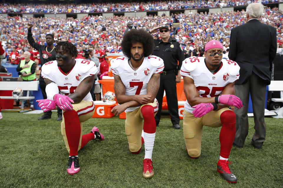 Colin Kaepernick kneels during the national anthem last season, alongside two of his teammates, Eli Harold (left) and Eric Reid (right). (Getty Images)
