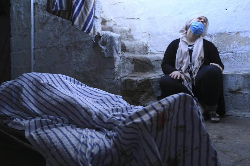 A relative cries by the body of a woman killed in shelling by the Turkish army in the town of Qamishli, Syria: AP