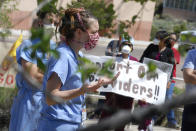 In this photo taken May 8, 2020, medical staff from Rehoboth McKinley Christian Hospital hold a protest over working conditions and depleted staff in Gallup, N.M. Many nurses and doctors say staffing at the hospital was inadequate because of hospital CEO David Conejo's move to cut back on nurses in the first week of March to offset declining hospital revenues after elective surgeries were suspended. They voiced their discontent at the recent protest calling for his resignation. (AP Photo/Morgan Lee)