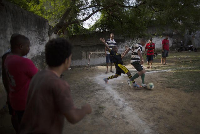 In this May 3, 2014 photo, players fight for the ball during an amateur soccer match in the Mangueira shantytown of Rio de Janeiro, Brazil. The government says it wants to use the upcoming World Cup to convince international visitors to keep coming back to Brazil after the tournament ends. (AP Photo/Leo Correa)