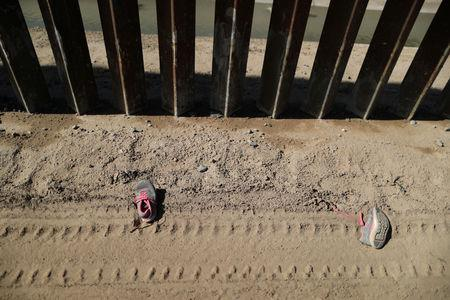 A pair of discarded shoes is seen next to the U.S.-Mexico border fence in El Paso, Texas, U.S., March 6, 2019.  REUTERS/Lucy Nicholson/Files