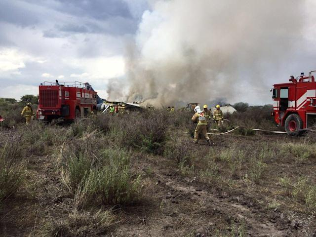<p>Firefigters and rescue personnel work at the site where an Aeromexico-operated Embraer passenger jet crashed in Mexico's northern state of Durango, July 31, 2018, in this picture obtained from social media. (Photo: Proteccion Civil Durango via Reuters) </p>