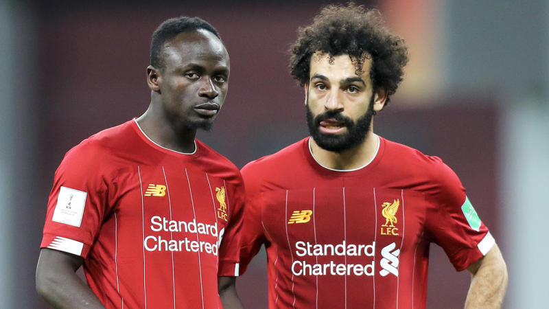 Liverpool's Sadio Mane (L) speaks with midfielder Mohamed Salah during a match.