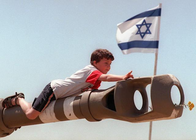<p>An Israeli youth stretches to flick an insect off the barrel of a howitzer during a weapons show on Israel's 50th anniversary, in the West Bank settlement of Efrat, April 30, 1998. It is not known who placed a yellow flower in the weapon's muzzle. (Photo: Jacqueline Larma/AP) </p>