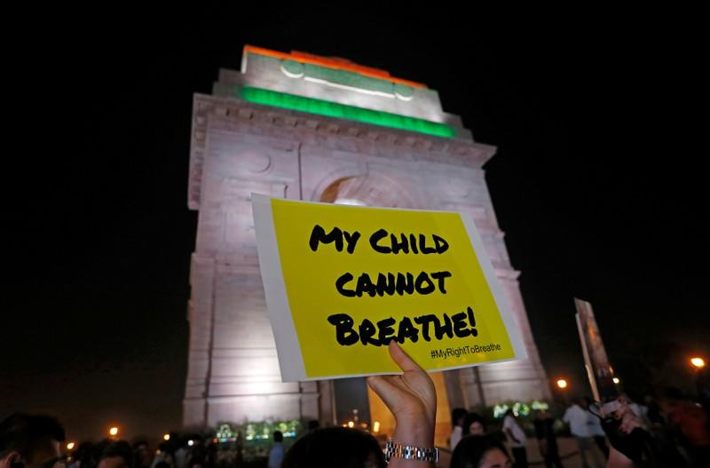 FILE PHOTO: A protestor holds a placard in front of the India Gate during a protest demanding government to take immediate steps to control air pollution in New Delhi