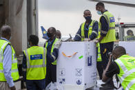 FILE - In this March 3, 2021, file photo, AstraZeneca COVID-19 vaccines are received by airport workers at the airport in Kigali, Rwanda. The COVAX global initiative is providing vaccines to poorer countries lacking the clout to negotiate for them on their own, but on March 25, COVAX announced a major setback in its vaccine rollout because a surge in infections in India had caused the Serum Institute of India to cater to domestic demand, resulting in a delay in global shipments of up to 90 million doses. (AP Photo/Muhizi Olivier, File)