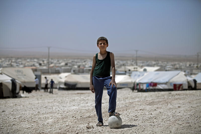 In this April 17, 2014, file photo, Syrian refugee Moath Kabesh poses with his soccer ball at Zaatari refugee camp, near the Syrian border in Mafraq, Jordan. Aleksander Ceferin, the head of European soccer's governing body and Jordan's Prince Ali have inaugurated a full-size soccer pitch in Jordan's largest camp for Syrian refugees. Organizers say the pitch is meant to give a sense of normalcy to 80,000 residents of Zaatari, which was set up in 2012, a year after the start of the Syria crisis (AP Photo/Khalil Hamra, File)