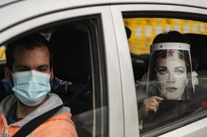 Marisol Aro, wearing a face shield with an image of Wonder Woman, looks out from a car window, amid the new coronavirus pandemic in Santiago, Chile, Saturday, June 27, 2020. Aro's husband bought her the face shield who has since been infected with the new coronavirus and is now intubated in an intensive care unit. (AP Photo/Esteban Felix)