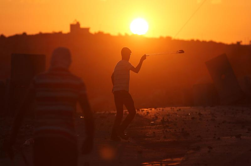 A Palestinian demonstrator uses a sling shot to throw a stone towards Israeli security forces during clashes on September 19, 2014, in the West Bank village of Silwad