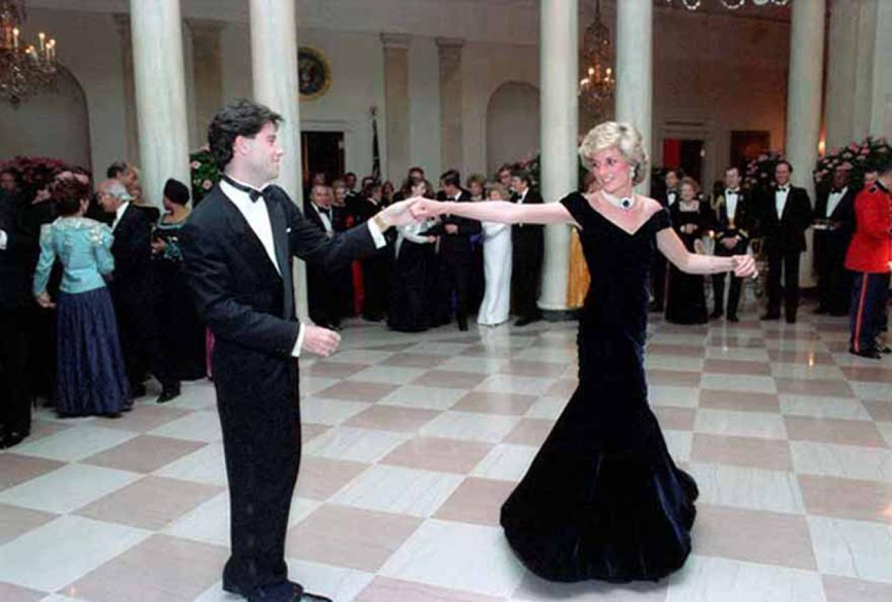 <p>Princess Di was the belle of the ball at the White House in the mid-80s in an off-the-shoulder velvet ballgown. This photo, depicting John Travolta spinning the royal around the dance floor, showed just how beautiful the fishtail skirt design was. <i>[Photo: Rex]</i></p>