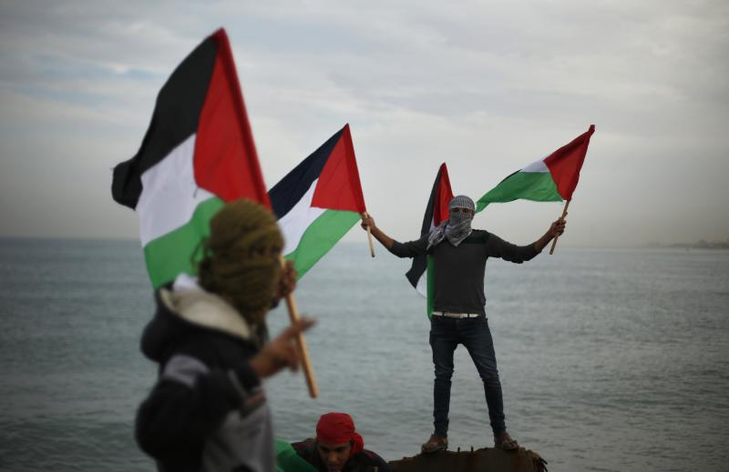 Palestinians wave national flags during a protest against the blockade on Gaza, at the seaport of Gaza City