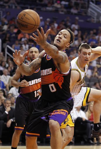 Phoenix Suns forward Michael Beasley, center, struggles to gain control of a ball before it lands out of bounds as Suns guard Kendall Marshall, left rear, and Indiana Pacers forward Tyler Hansbrough, right rear, look on during the first half of an NBA basketball game, Saturday, March 30, 21013, in Phoenix. (AP Photo/Paul Connors)