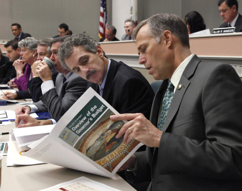 FILE - In this Jan. 13, 2011, file photo California assembly members Mike Feuer, D-Monterey Park, left, and Jared Huffman, D-San Rafael, look over the Legislative Analyst's report on California's proposed 2011-12 budget during a budget hearing at the Capitol in Sacramento, Calif. California has borrowed $9.8 billion to keep unemployment insurance payments flowing, and owes the federal government a $362 million interest payment by the end of September. (AP Photo/Rich Pedroncelli, File)