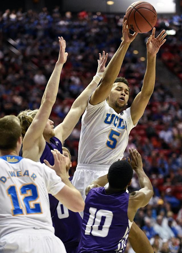 UCLA guard Kyle Anderson (5) throws an outlet pass after being confronted by Stephen F. Austin guard Trey Pinkney in a third-round game in the NCAA college basketball tournament, Sunday, March 23, 2014, in San Diego. (AP Photo/Denis Poroy)