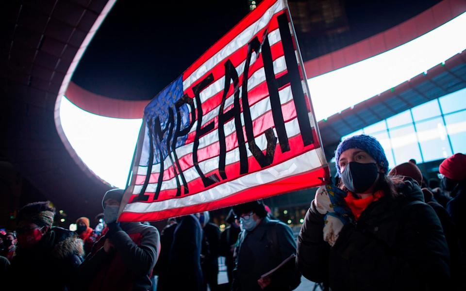 Two masked people hold up an American flag with impeach emblazoned on it - Kena Betancur/AFP via Getty Images