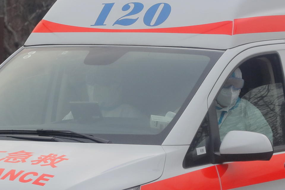 Fully protected medical staff drive an ambulance outside Beijing Ditan Hospital, in Beijing.