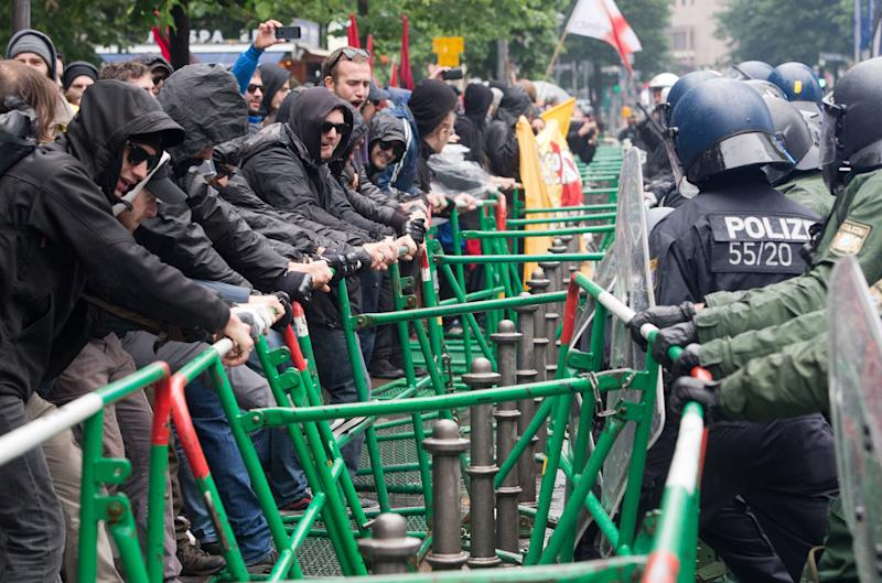 Members of the Blockupy movement shake a police fence in the inner city of Frankfurt/Main, Germany, Friday, May 31, 2013. The anti-capitalist protesters rallied in front of ECB to protest against austerity measures. (AP Photo/dpa,  Boris Roessler)