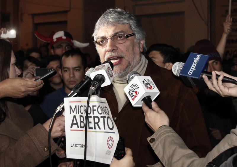 "Paraguay's former President Fernando Lugo talks through the ""open microphone"" of the Public Television, surrounded by reporters and followers in downtown Asuncion, Paraguay, in the early hours of Sunday, June 24, 2012. Lugo spoke in a pre-dawn special televised ""open microphone"" program hosted by the state-funded Public Television channel that was created by his government, to denounce his ouster as a ""parliamentary coup"". (AP Photo)"