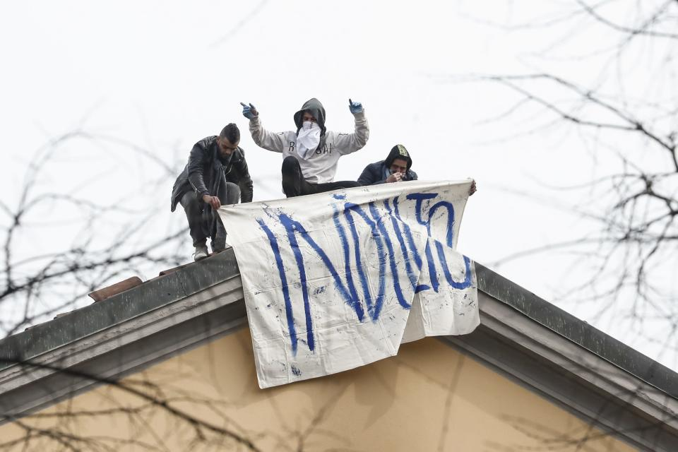 Inmates unfold a banner reading in Italian Pardon as they stage a protest against new rules, including the suspension of relatives' visits, to cope with coronavirus emergency, on the roof of the San Vittore prison in Milan, Italy, Monday, March 9, 2020. Italy took a page from China's playbook Sunday, attempting to lock down 16 million people — more than a quarter of its population — for nearly a month to halt the relentless march of the new coronavirus across Europe. (AP Photo/Antonio Calanni)