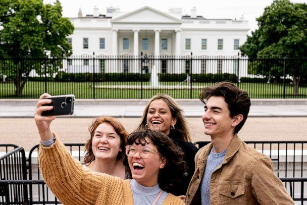 PHOTO: From left, Eliana Lord, Carly Mihovich, Stephanie Justice, and Nick Hansen, visiting from Columbia, S.C., take a photo at Lafayette Park, across the street from the White House, after it reopens in a limited capacity in Washington, May 10, 2021. (Andrew Harnik/AP)