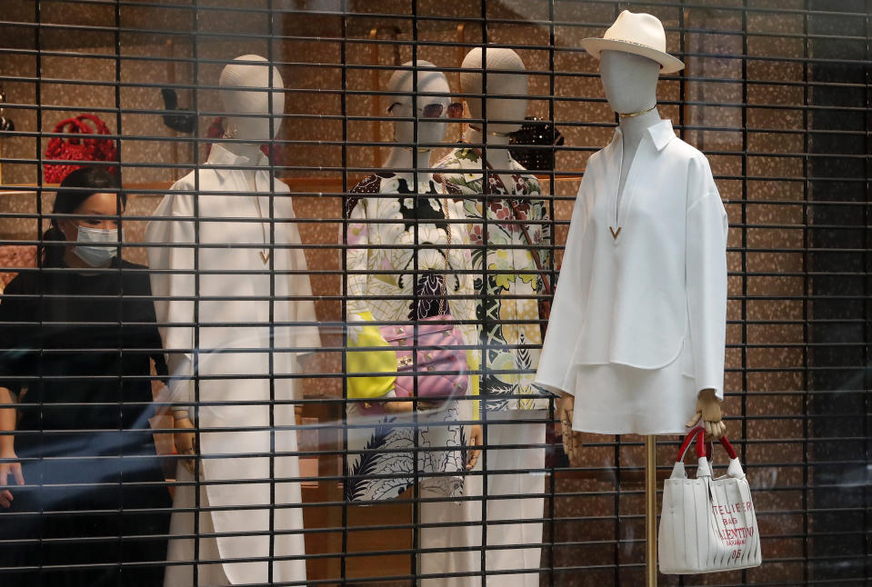 A woman wearing a face covering due to the COVID-19 pandemic decorates a shop window in London, Wednesday, Feb. 17, 2021, as the lockdown continues. (AP Photo/Frank Augstein)