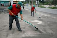 Employees sweep the entrance of a gas station covered with ash after Guatemala's Fuego volcano erupted violently, in Guatemala City, Guatemala June 3, 2018. REUTERS/Luis Echeverria