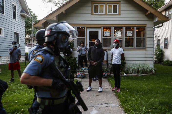 Bystanders watch as police walk down a street May 28, 2020, in St. Paul, Minn. Protests over the death of George Floyd, a black man who died in police custody, broke out in Minneapolis for a third straight night. The image was part of a series of photographs by The Associated Press that won the 2021 Pulitzer Prize for breaking news photography. (AP Photo/John Minchillo)