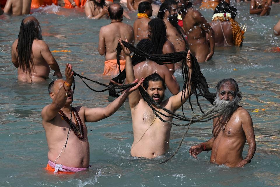 Naga Sadhus (Hindu holy men) take a holy dip in the waters of the River Ganges on the Shahi snan (grand bath) on the occasion of Maha Shivratri festival during the ongoing religious Kumbh Mela festival in Haridwar on March 11, 2021. (Photo by Prakash SINGH / AFP) (Photo by PRAKASH SINGH/AFP via Getty Images)