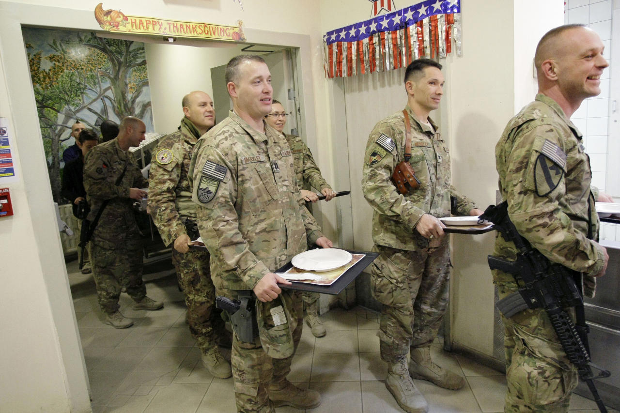 U.S. soldiers and NATO service members stand in line for a Thanksgiving meal at the U.S.-led coalition base in Kabul, Afghanistan, Thursday, Nov. 22, 2012. The dining hall at the U.S.-led coalition base in the Afghan capital served up mac-and-cheese along with traditional Thanksgiving Day fixings. (AP Photo/Musadeq Sadeq)